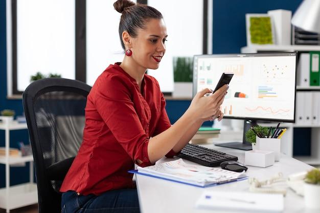 Felice allegra imprenditrice eccitata che scrive su smartphone, seduta alla scrivania nel posto di lavoro dell'azienda. messaggistica dell'imprenditore tramite telefono cellulare. impiegato che legge il testo sul telefono.