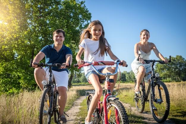 Famiglia allegra felice con la figlia che guida le biciclette in prato al giorno soleggiato