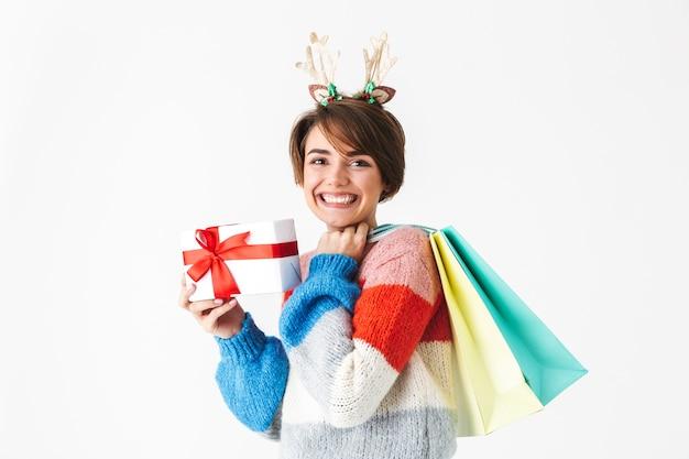 Felice ragazza allegra che indossa un maglione in piedi isolato su bianco, tenendo presente la casella, portando le borse della spesa