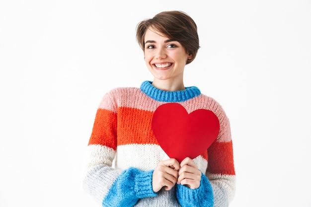 Felice ragazza allegra che indossa un maglione in piedi isolato su bianco, tenendo il cuore rosso