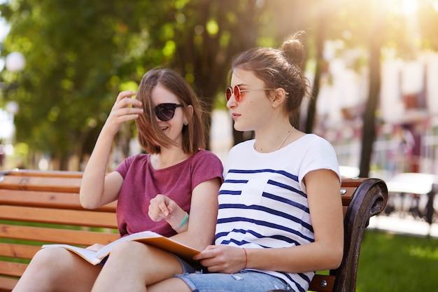 Ragazze allegre felici sono nel parco per godersi l'atmosfera estiva e leggere le ultime notizie dal mondo.