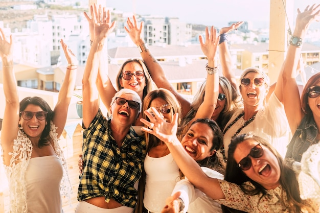 Felice e allegro gruppo di amiche che ballano e si divertono insieme sul tetto di casa