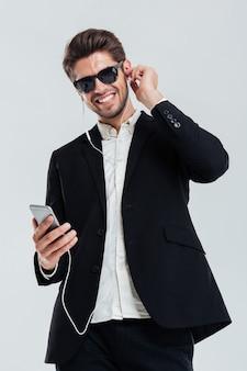 Felice allegro bell'uomo d'affari che ascolta musica con auricolari e smartphone su un muro grigio