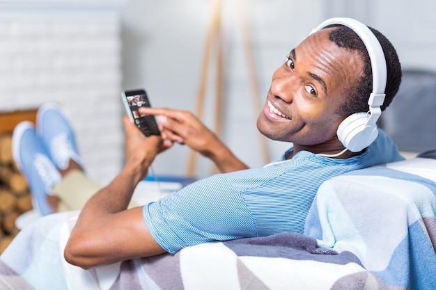 Uomo bello allegro felice che indossa le cuffie e ti sorride mentre ascolti la musica