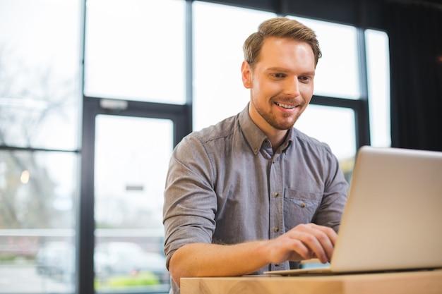 Felice allegro simpatico uomo seduto davanti al laptop e digitando mentre lavorava come libero professionista