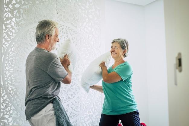Coppie caucasiche senior anziane allegre felici giocano a casa con i cuscini in camera da letto