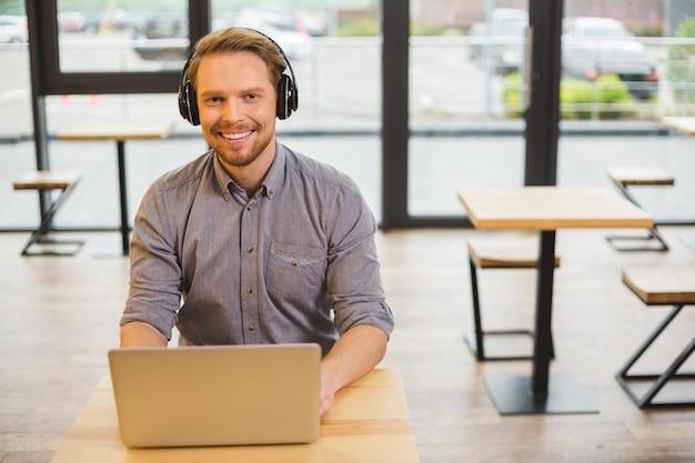 Felice allegro piacevole uomo seduto nella caffetteria e sorridente mentre si lavora lì sul computer portatile