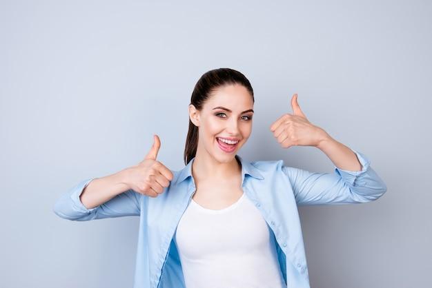 Donna allegra felice in camicia blu che mostra i pollici aumenta lo spazio grigio isolato