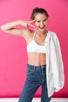 Donna allegra felice in top bianco e jeans che mostrano la lingua e il segno di vittoria isolato sulla parete rosa