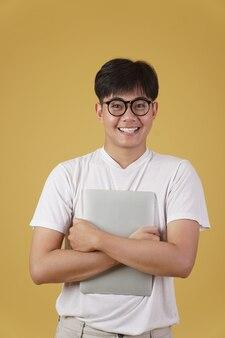 Felice allegro giovane studente asiatico nerd uomo vestito con indifferenza indossando occhiali tenendo il computer portatile isolato