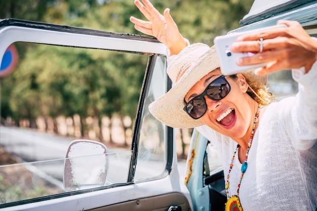 Felice e allegra giovane bella donna caucasica scatta una foto selfie fuori dal suo furgone retrò godendosi il viaggio e lo stile di vita di viaggio - stile di vita delle vacanze estive