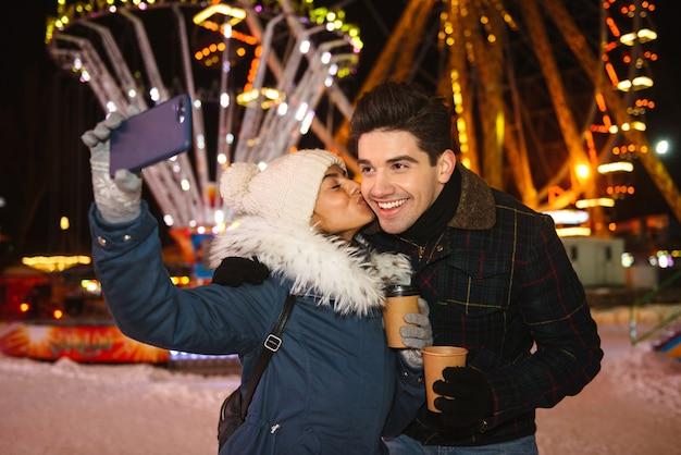 Giovani coppie allegre felici divertendosi al parco di pattinaggio su ghiaccio di notte, tenendo tazze di caffè da asporto, prendendo un selfie