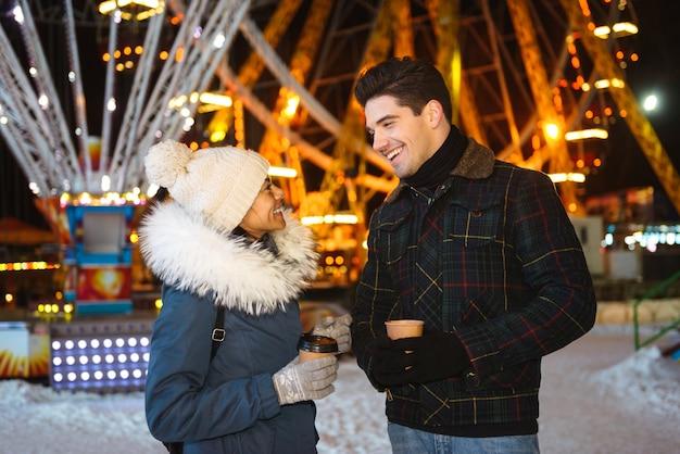 Giovani coppie allegre felici divertendosi al parco di pattinaggio su ghiaccio di notte, tenendo tazze di caffè da asporto