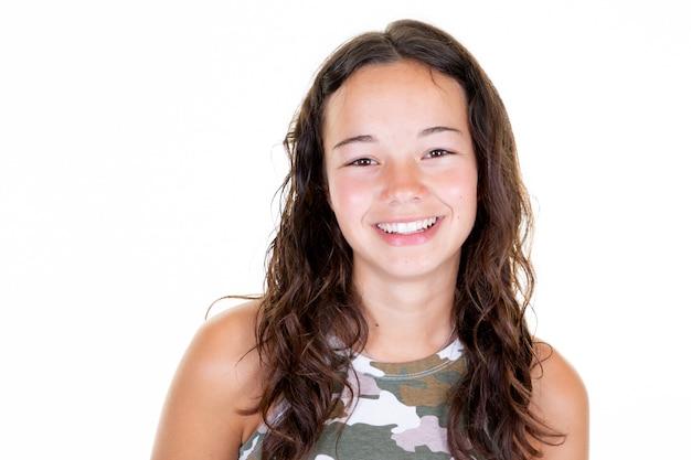 Giovane ragazza allegra felice dell'adolescente con i bei denti del fronte che ride guardando macchina fotografica sul fondo della luce bianca