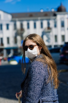 Felice allegra giovane donna in maschera medica facciale mentre si trova in strada in città.