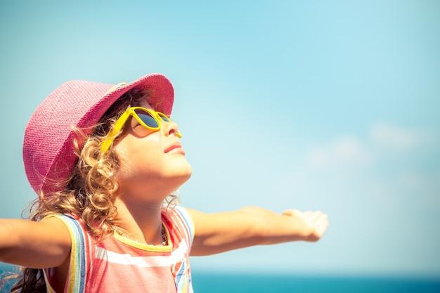 Bambino felice contro il fondo del cielo blu.