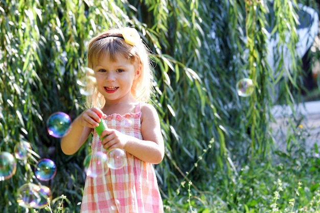 Bambino felice che soffia bolle nel parco naturale