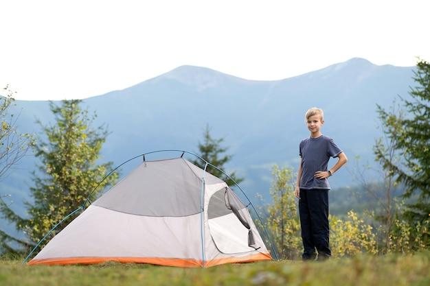 Bambino felice che riposa vicino a una tenda turistica in un campeggio di montagna che si gode la vista