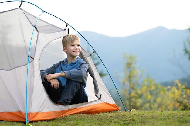 Ragazzo felice del bambino che riposa in una tenda turistica al campeggio della montagna che gode della vista della natura bella estate. escursionismo e stile di vita attivo concetto.