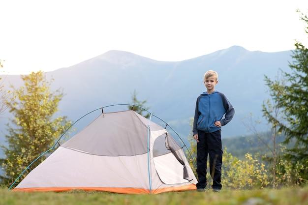 Bambino felice in piedi vicino a una tenda turistica al campeggio di montagna