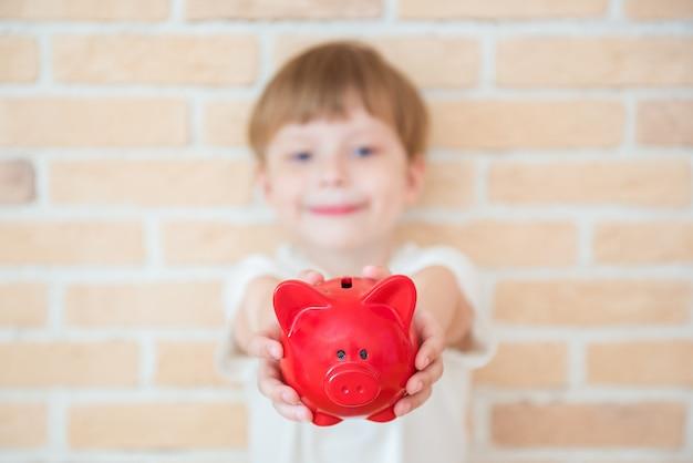Il ragazzo felice del bambino sta con un porcellino salvadanaio in sue mani. successo, concetto di business creativo e innovazione