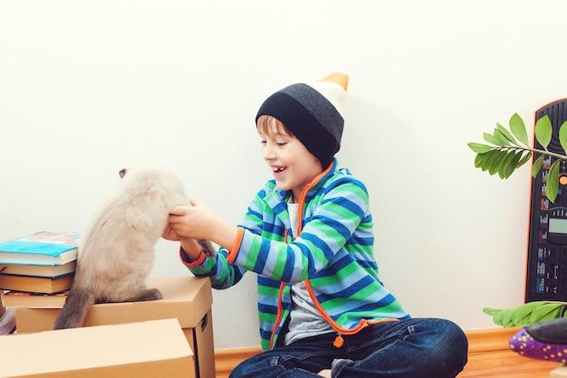 Bambino felice e gatto che si divertono insieme al giorno del trasloco nella nuova casa.