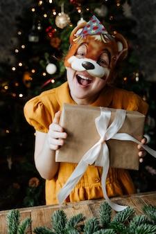 Bambino felice sotto l'albero di natale con un regalo.