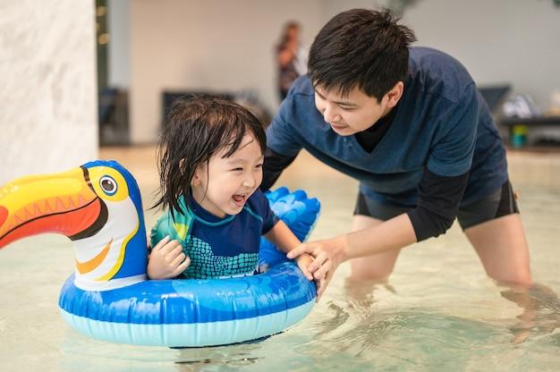 Bambino felice e papà con piscina su anello gonfiabile a forma di bucero divertendosi in una piscina