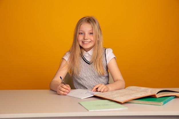 Il bambino felice che fa i compiti seduto ha isolato lo sfondo giallo brillante.