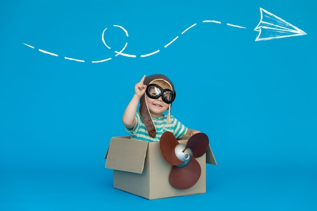 Il bambino felice sogna di diventare un pilota contro il muro di carta blu.