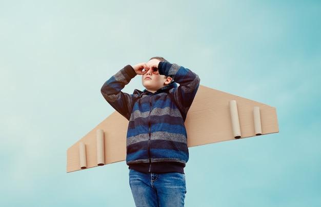 Bambino felice sogna di viaggiare e ragazzo che gioca con aeroplano di ali di carta giocattolo