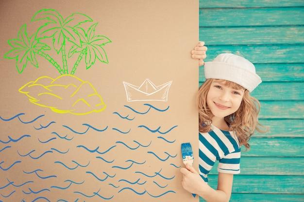 Bambino felice vestito da marinaio che disegna un'isola su una parete di cartone
