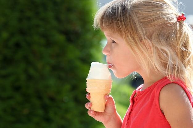 Bambino felice che mangia il gelato sulla natura del parco