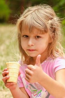 Bambino felice che mangia il gelato all'aperto nel parco