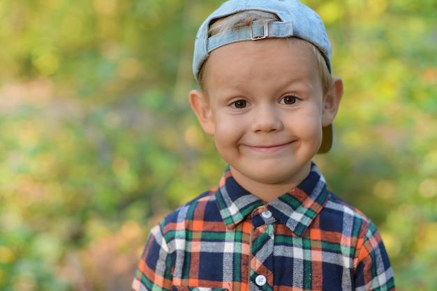 Bambino felice dell'aspetto europeo nella foresta d'autunno