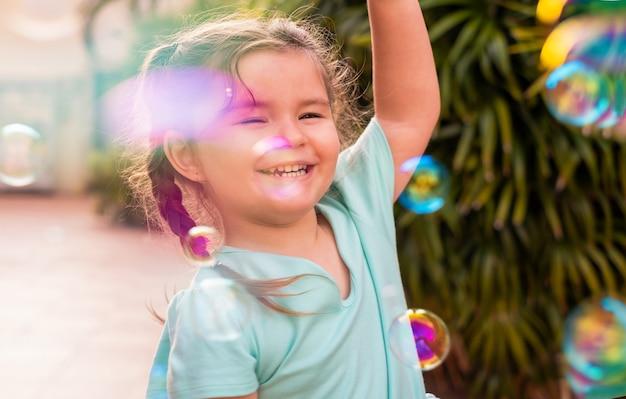 Ragazza felice del bambino che cattura le bolle di sapone