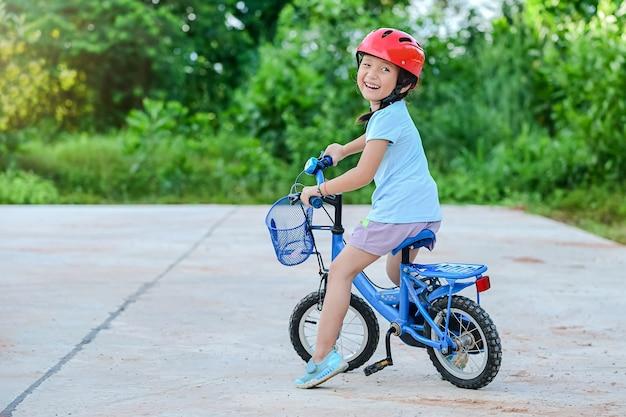 Ragazza felice del bambino in bicicletta nel parco del villaggio per la sera con esercizio di luce del tramonto.