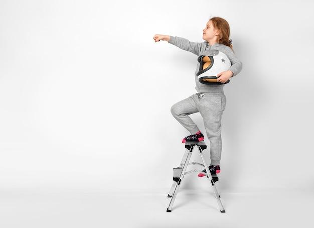 Bambina felice vestita con un costume da astronauta in piedi su una scala a pioli.