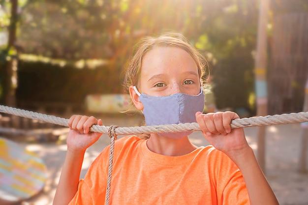Ragazza bambino felice con la maschera per il viso nel parco giochi