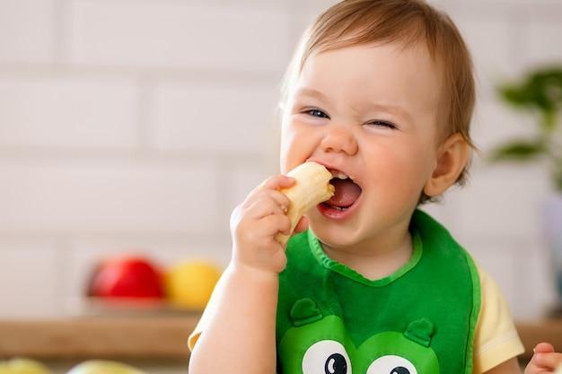 La ragazza felice del bambino nella cucina mangia i frutti saporiti, arance dolci.