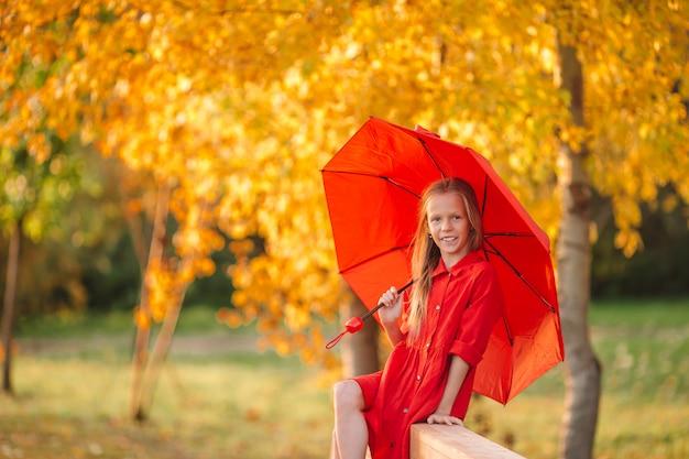 La ragazza felice del bambino ride sotto l'ombrello rosso