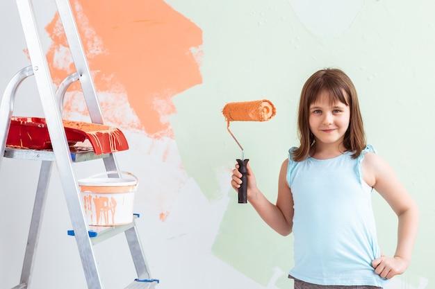 La ragazza felice del bambino dipinge il muro con vernice arancione,