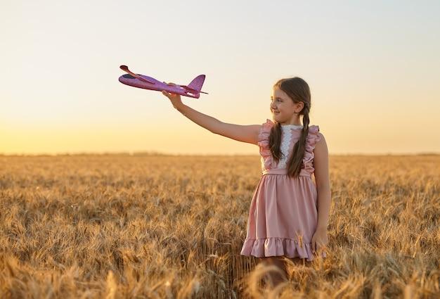 Bambino felice, ragazza che gioca con l'aeroplano giocattolo sul campo di grano estivo. la piccola figlia sogna di volare. bambino spensierato che gioca all'aperto