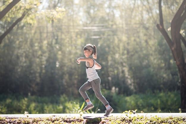 Ragazza felice del bambino che corre nel parco in estate in natura. bagliore di luce solare calda. il piccolo asiatico sta correndo in un parco. sport all'aria aperta e fitness, esercizio fisico e apprendimento della competizione per lo sviluppo del bambino.