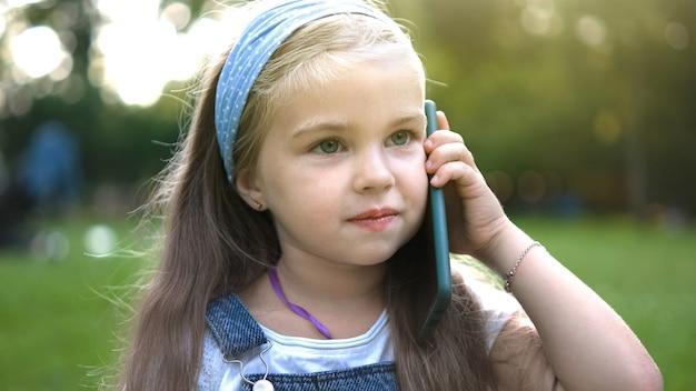 Ragazza felice del bambino che comunica sul telefono cellulare nel parco estivo.