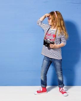 Turista felice della ragazza del bambino con la retro macchina fotografica alla parete blu.
