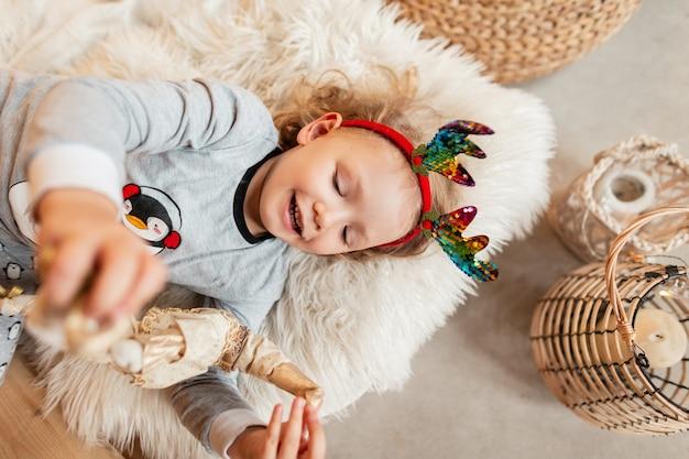 Bambina felice con corna di cervo di natale in pigiama alla moda si trova sul letto e gioca con un giocattolo durante le vacanze invernali, viste dall'alto