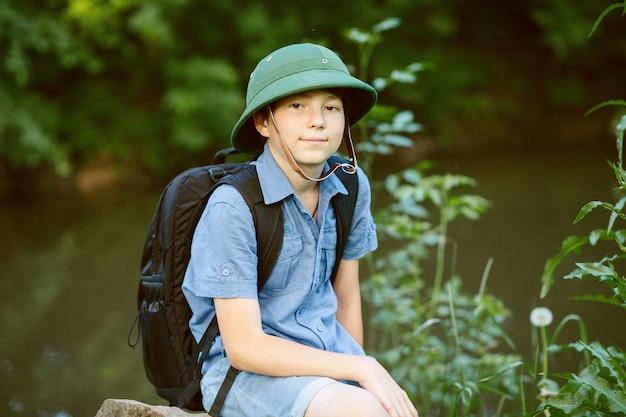 Il bambino felice fa un'escursione con lo zaino nella natura estiva summer