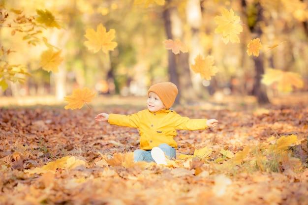 Bambino felice che si diverte nella sosta di autunno. bambino divertente che gioca all'aperto.
