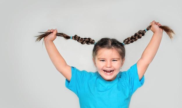 Bambino felice che tiene le trecce e ride su sfondo grigio